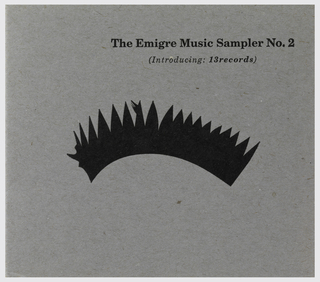 "Cover:  two-tone, two-fold cardboard packaging with gray on the outside and orange on the inside.  ""The Émigré Music Sampler No. 2"" in bold, black font in top right corner of cover.  ""(Introducing:  13 records)"" underneath title in italicized black font.  The center of the outside cover is occupied by  black eyelashes or skewed tiara-like design. CD:  black plastic"