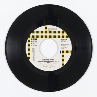 Black plastic record album. Black record with label with vertical and horizontal lines of checkered black and yellow. Logo at left: EMI / MAN / HAT / TAN inside squares; lower section: RICHARD MARX / ENDLESS SUMMER NIGHTS (4:11) / (Edit) / (Richard Marx) Chi-Boy Music-ASCAP / Produced by Humberto Gatica for / Hum Productions, Inc. / ? ©1988 EMI-Manhattan Records, / a division of Capitol Records, Inc. Right side: 45 RPM / STEREO / P-B-50113 / 241900A / NOT FOR SALE / 2.