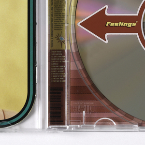 "CD cover design for David Byrne's album ""Feelings"" within clear plastic CD case; CD insert contains six pages. Cover: Close-up color photo reproduction of doll's head modelled after David Byrne (content expression) against blue background within rounded triple-line border (in black, orange, black).  This packaging features happy, angry, sad, and content David Byrne dolls; the packaging includes a sophisticated, color-coded ""David Byrne Mood Computer (printed on and under the disc) that lets you determine your current feelings.  The type was made as an actual model and then photographed. Page 1: Title page, imprinted Feelin/gs David/Byrne"" at center.  Page 2. black and white photo reproduction of doll showing anger. Page 3/4: Credits imprinted, left, ""ALL SONGS WRITTEN BY/ DAVID/ BRYNE/.../PUBLISHED BY/ MODLY FIG MUSIC BMI/.... At center, imprinted, ""DESIGN BY/ SAGMEISTER, INC. NEW YORK, NY/ PHOTOGRAPHY BY TOM SCHERLITZ...DAVID BYRNE DOLL CLOTHES BY/ ADELLE LUTZ WITH MICHAEL DAUBE..."" At lower right, imprinted ""FOR MORE INFORMATION FO TO:/ www.luakabop.com"". Page 5: Black and white photo reproduction of doll expressing sadness. Page 6. List of songs in two columns.  From ""FUZZY FREAKY....THEY ARE IN LOVE"".  Back of CD insert: Color photo reproduction of doll expressing happiness against yellow background.  Double line border (in green and black) around page.   CD: Red arrow across center and imprinted in white: ""Feelings DAVID BYRNE"".   Underneath CD: Four pictures of doll showing four extreme emotions depicted in CD insert.  Pictures superimposed on color wheel corresponding to color chart on top. Color chart shows gradation from blue, green, red, to yellow which signifies a certain degree of emotional state (from pale blue=Relaxed to pale yellow=Pleased).    Back of case: Color photo reproduction of full view of doll wearing jacket and black pants.  On pink background, list of songs with color squares below showing the type of feeling each song produces."