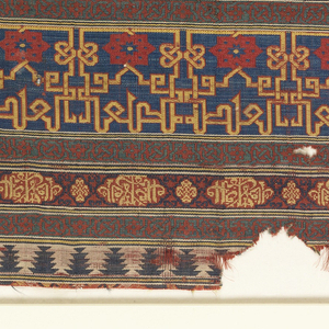 """Fragment of woven silk with horizontal bands of geometric pattern including various interlace patterns, eight-pointed stars, and kufic script in the form of lobed medallions. The script is translated as """"Sucess and prosperity"""" and """"Beatitude."""""""