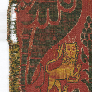 Irregularly shaped fragment of woven silk. Large, curving leaves form an inverted heart-shaped framework resolving in a center stem surmounted by a cone. Confronted rampant crowned lions flank the center stem. In red, yellow and white on a deep green satin ground.