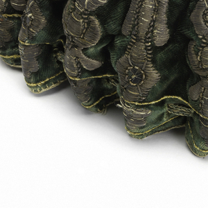 Green velvet bag lined with leather, with green draw string and metal tassels. Embroidered on the sides with a raised columnar design in silver. The bottom is embroidered with the coat of arms of the City of Paris in coral-colored silk and metal threads.