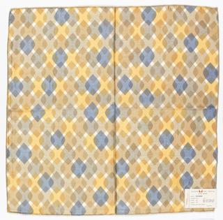 Diamonds with rounded side corners overlapping each other in rows.  Printed in orange, blue, tans on white. Serged on all sides.