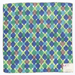 Rounded diamond shapes overlapping each other in columns and rows to form an argyle-like pattern. The colors are translucent so the overlapped areas show as darker or mixed colors. Printed in brown, dark blue, light blue, dark green, and light green on white. Serged on all sides.