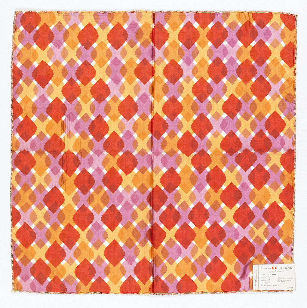 Diamonds with rounded side corners overlapping each other in rows. Printed in oranges, red, pink, on white. Serged on all sides.