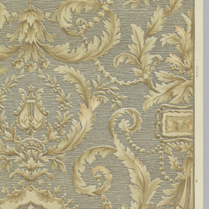 Ground of slate blue, horizontal coarse weave with tan and peach stylized curled foliage and small floral chains.