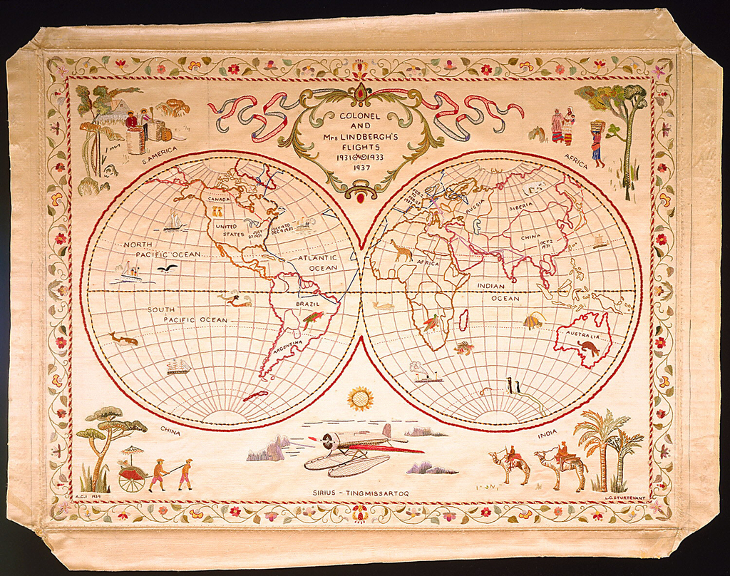 The globe shown in two hemispheres, showing the flights of Colonel and Mrs. Lindberg in 1931, 1933 and 1937. There are scenes in each corner labeled S. America, Africa, China, and India.  At the bottom center, there is a plane labeled the Sirius-Tingmissartoq. The entire map is enclosed by a scrolling floral vine.