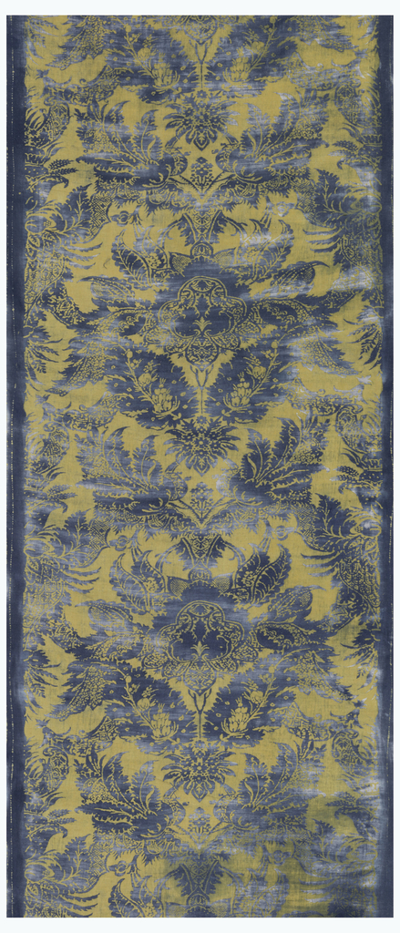 Yellow cotton printed in blue in a Renaissance-type pattern of large flowers and leaves with secondary ornamentation in an ogival arrangement.