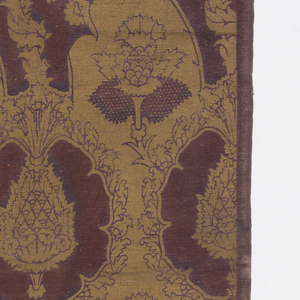 """Block-printed twill fabric in gold on purple showing """"pomegranate"""" design in the style of 15th century Venetian velvets."""
