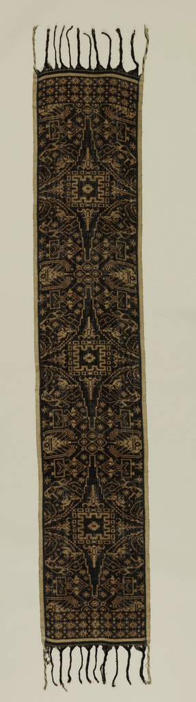 "Cotton textile created in the double ikat  or 'geringsing' technique showing a ""kota-mesir"" pattern (four-pointed star, notched internal pattern, divides piece into semi-circular segments). Semi-circles depict ""wayang patlikur isi"" motif (geometric wayang figure) and other figures. Wide border at end with geometric pattern. Design in tan on black. Fringed."