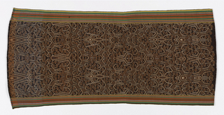 Cotton panel seamed at ends, probably to form a garment--either a loin cloth or ritual skirt (kain kebat). Design highly stylized, geometric hooked pattern in white and dull red on dark brown ground. Woven borders in narrow red, green, and black stripes run the length of piece