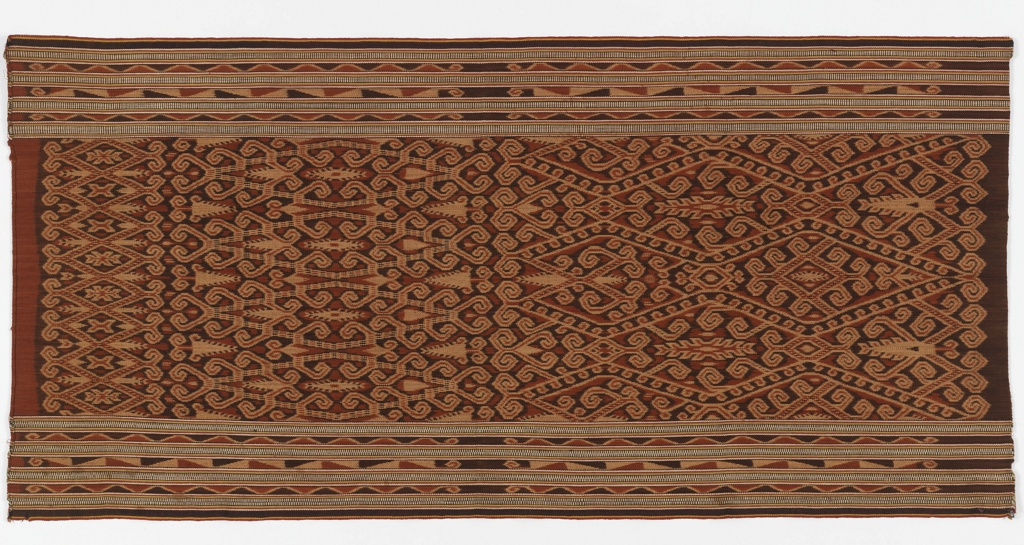 Kantu' woman's ritual skirt (kain kebat or bidang) with an all-over patterned field and striped borders on two sides. The field is densely covered by a pattern which can be divided into three sections where the pattern size is small, medium, and large. Each section has a variation of a vine on scroll-like diamond with the addition of what may be crawfish or plants. The borders consist of alternating stripes--ikat geometric pattern alternating with warp stripes (a zigzag variation on one side and short parallel lines on the other). In tan, dark brown, rust-red, ivory in addition to small amounts of yellow, blue-grey, red, and black.