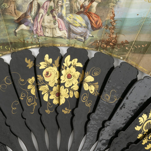Printed lithographic fan with hand-colored and gilded paper, and sticks of lacquered papier maché. Scene shows a country dance with costumes in the style of the 17th century. Sticks are decorated with painted floral decoration and motifs in gilt.