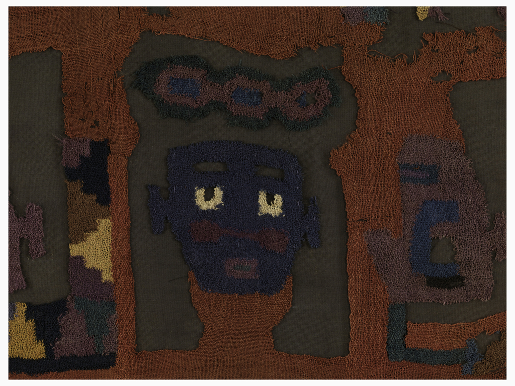 Fragment of a mantle with close-set horizontal rows of stylized warriors' heads, each with different headdress and color combinations. In the top row, upright front-facing heads alternate with upside down heads in profile. In the next row, upright heads in profile alternate with upside down front-facing heads. Rich muted shades of brown, gold, tan, blue, green, purple, and white on a rust-red ground.