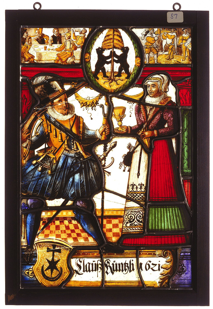 """Rectangular stained glass panel depicting a well-dressed couple; with one hand, man pulls a cord with tassel, and woman holds a gold goblet. Possible wedding portrait. Above couple, an oval crest showing two black bears flanking a yellow pine tree, between two scenes. On left: men dining and drinking (celebrating), on right: standing musicians. Below, left, a gold shield crest featuring a black symbol of a cross, star and crescent conjoined. To the right, an inscription: """"Clausskunklibzi"""" [?]"""