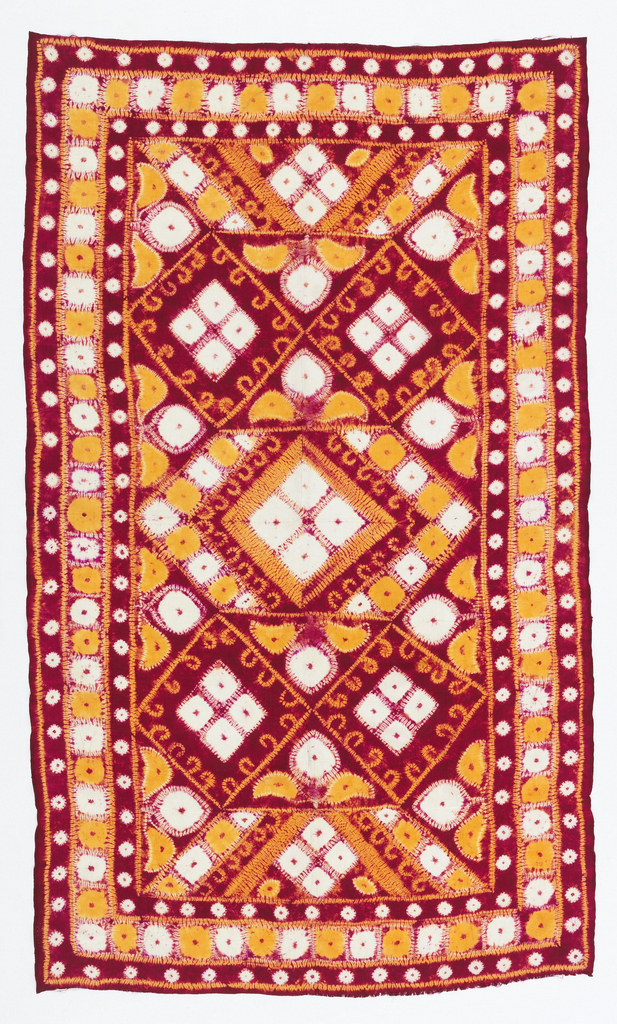 tied-resist dyed silk textile with a field filled with diamond shapes, border of large dots with guard borders of smaller dots. In red, orange and white.