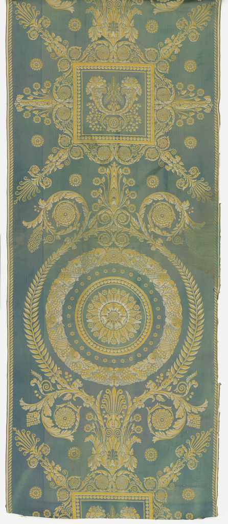 Length of silk furnishing fabric in the Empire style. Yellow and white design on a blue-green ground shows a wreath-like medallion alternating with a square radiating with leaf forms. Fabric contained within width. Both selvages present.