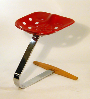 Cantilevered form consisting of red tractor seat mounted on curved, strap-like chrome-plated steel base with beechwood crossbar terminus as footrest.