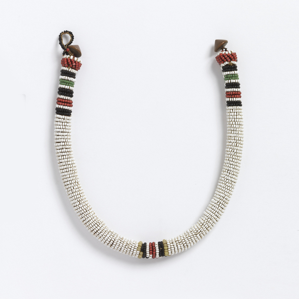 Tubular necklace with horizontal rows of white glass beads, with red, green and black stripes at the center front and back. Cone-shaped metal fastener.