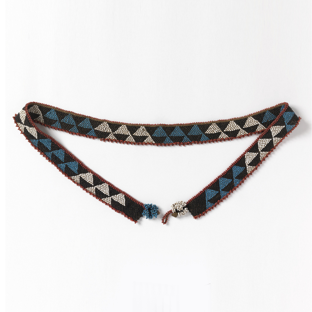 Long, narrow beaded belt with a design of opposing triangles in black, blue, and white, with red beads on long edges. Fastened with cone-shaped metal buttons.