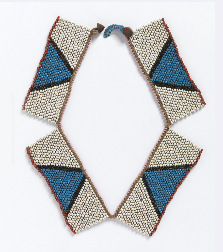 Necklace composed of four rectangular panels. Each has a white field with a blue triangle bordered in black. The upper edge is pink, and the lower edge of each rectangle is red. Fastened with cone-shaped metal buttons.