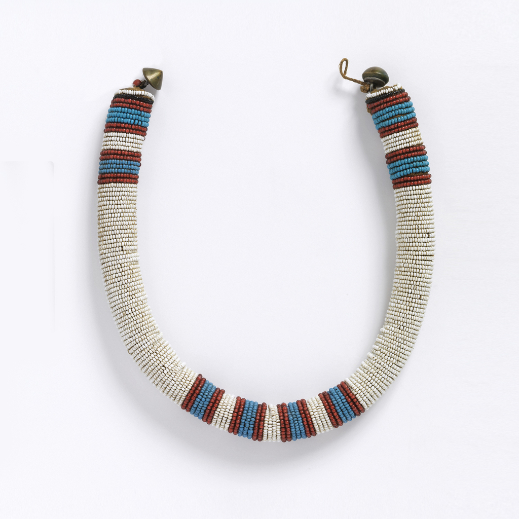 Tubular necklace with horizontal rows of white glass beads, with four red and blue stripes at the center front and back. Cone-shaped metal fasteners.