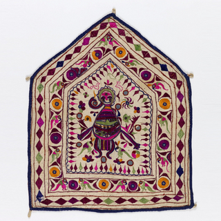 Wall hanging of woven natural cotton embroidered with silk in chain stitch and satin stitch and appliquéd with mirrors. Five pointed shape with a linen loop at each corner. Design showing a deity with four arms surrounded by mirrors, embroidered flowers and a frame of diamond shapes; an inner border with birds and mirrors set in circles; an outer border with running diamonds. Band of blue cotton sewn around edge.