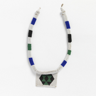 "Necklace of a type known as a ""love letter."" White tubular beaded neckalce banded with black, blue and green stripes. A white square suspended from the center front has a black hexagon with green triangular forms. The various color combinations and designs convey messages connected with courtship."
