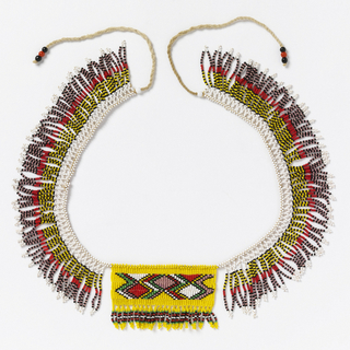 "Necklace known as a ""love letter.""  Bright yellow beaded rectangle with multicolored interlocking diamonds, suspended from a multicolor, beaded, fringed collar. The various color combinations and designs convey messages connected with courtship."