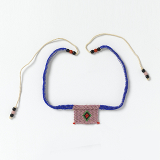 "Necklace known as a ""love letter.""  Tan beaded square with red, green and black concentric diamonds, suspended from bright blue beaded cords. The various color combinations and designs convey messages connected with courtship."