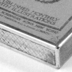 """Rectangular, with beige and black enameled front resembling the cover of a January issue of Scribner's Magazine. The right long side has incised, vertical lines intended to resemble pages. Reverse is undecorated except for the inscription """"W.W. Hallock."""" Lid hinged on left. Striker of incised hatch marks on bottom.   Sterling 2867"""