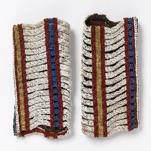 Bracelet for the upper arm, solidly beaded with trade beads in white, blue, yellow, and red in simple striped patterns.