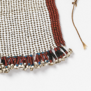 Rectangular panel of beads attached to a cord, solidly beaded with trade beads with a white ground, red borders, and fringed with black, blue and white tassels.