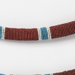 Belt made in two pieces to be fastened at sides with button and thong closures. Heavy cord solidly covered with red beads, with stripes of blue and white.