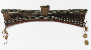 Rows of beads in red, green, white and black are attached to the top and bottom of a shaped band of fur. Three small brass knobs at the center top. Leather thongs attached at edges, for tying on to head.
