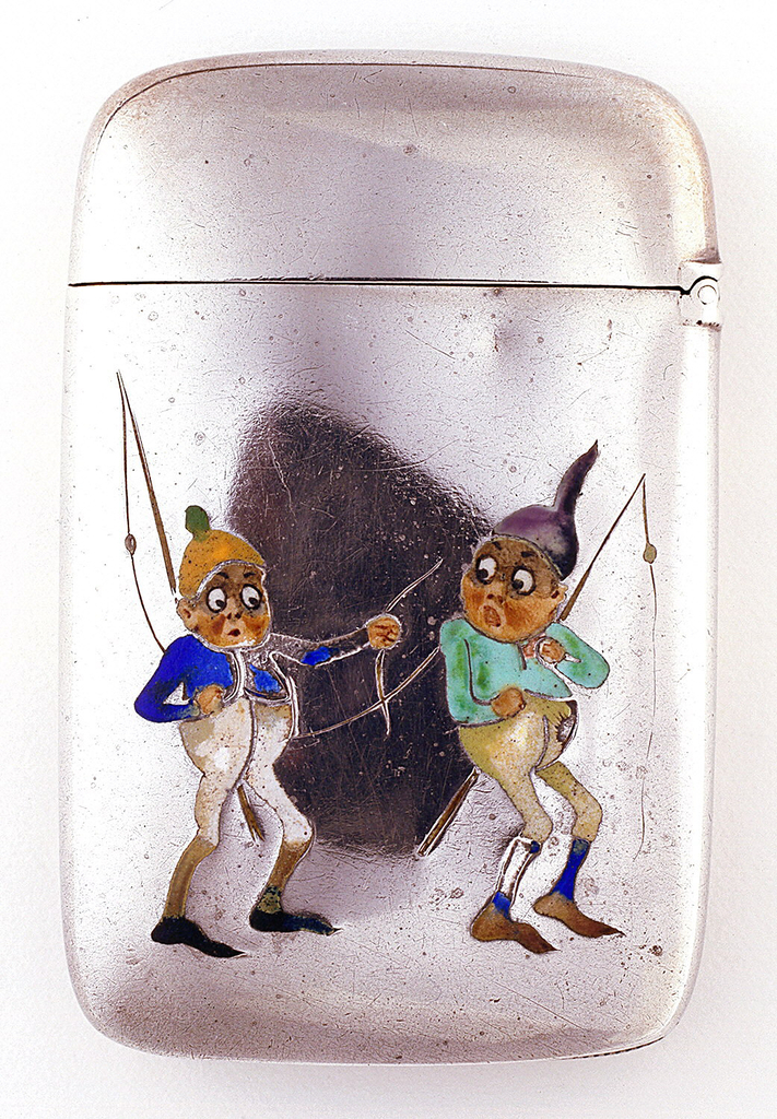 """Rectangular, with rounded corners, the front decorated with two enameled images of elfin-like """"Brownies"""" characters, each holding a fishing pole. Both with wide eyes, rosy cheeks, protruding bellies and long, skinny legs, the figure on the left, gazing towards the right, wears a yellow cap with green pom-pom, blue shirt, white knickers, brown stockings, pointed black shoes; figure on the right, gazing left towards other character, wears a purple and black pointed cap, green shirt, off-white knickers, blue stockings, pointed brown shoes. Reverse is undecorated. Lid is hinged on right. Recessed striker on bottom."""