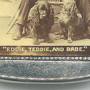 "Rectangular, curved top and bottom, featuring sepia toned photographic image of man in dark suit and bowler hat, seated in white wicker chair, gesturing towards a pair of small, long-haired spaniels at his feet, inscribed beneath ""Eddie, Teddie, and Babe,"" reverse inscribed ""Greetings, Eddie Gosnell, Original 12 Points Saloon. 1267 Maple Ave., Terre Haute, Ind.,"" inscribed in fine print just below ""Roberson-Putnam Co, Chicago."" Lid hinged on side. Striker in recessed groove on bottom."