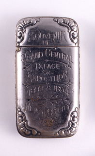 """Oblong, with rounded and raised decoration at corners, inscribed """"Souvenir of Grand Central Palace Exposition 1893 & 1894 New York City,"""" delicate, incised decoration interspersed among text. On reverse is incised image of the American flag. Lid hinged on left. Striker on bottom."""