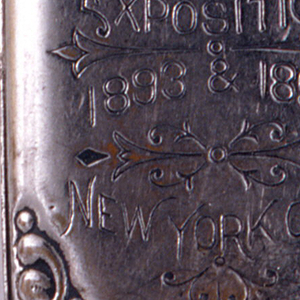 "Oblong, with rounded and raised decoration at corners, inscribed ""Souvenir of Grand Central Palace Exposition 1893 & 1894 New York City,"" delicate, incised decoration interspersed among text. On reverse is incised image of the American flag. Lid hinged on left. Striker on bottom."