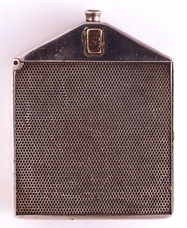 In the form of a Rolls Royce radiator grille, with simulated perforations on front and reverse of body. The unadorned, canted lid displays car's logo, two overlapping R's in red enamel, on both front and reverse. At top of lid is a radiator cap. Lid hinged on side. Striker recessed in bottom.