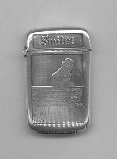 """Rectangular, rounded corners and sides, featuring raised decoration of man in hat, jacket and waistcoat behind waist-high wood fence, 3/4 view in lower left corner of grimacing dog facing the smiling man on opposite side, inscribed between the two """"Tis easy enough to be pleasant when life goes by with a song but the man worth while is the man who will smile when everything goes dead wrong."""" Inscribed in raised letters on lid """"Smile!"""" Reverse slightly concave. Lid hinged on side. Striker on bottom."""