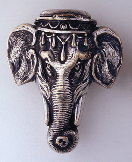 In the form of an elephant's head with large ears, long trunk curled at end, tusks, and jeweled ornament draped across brow, identical face on reverse. Small round and flat lid on top hinged on reverse. Striker on lid.