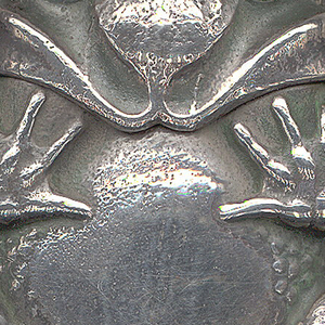 In the shape of a toad, its feet folded up against body, its belly smooth, the back textured with bumps, some green patination in crevices. Hinge attached to top of head. Head (lid) flips backwards, hinge on back. Sides of thighs have hatch marks likely intended to serve as strikers.