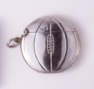 "In the form of a round, British football, front ribbed and laced down the center. Reverse ribbed, inscribed ""Strike boldly, then your light will shine clear. Affly."" Lid (upper section of ball) hinged on left side. Link attached on left side. Striker recessed in bottom"