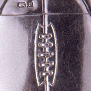 """In the form of a round, British football, front ribbed and laced down the center. Reverse ribbed, inscribed """"Strike boldly, then your light will shine clear. Affly."""" Lid (upper section of ball) hinged on left side. Link attached on left side. Striker recessed in bottom"""