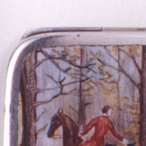 Rectangular, rounded corners, snuff-box type container. Lid decorated with polychrome enamel scene of English-style hunt situated on dirt road in wooded landscape: central female figure wears black waistcoat, long skirt and hat, riding side-saddle on brown horse, flanked by two male riders in red waistcoats and jodphurs, male on left on black horse, male on right on black and white horse, group of riders featured in right background, hunting hounds running beside horses. Lid hinged on back panel. Thumb catch on front edge of lid. Loop attached to right panel. Incised striker on front panel.