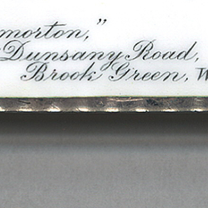 """Rectangular, featuring black and white enamel decoration, text/image reads horizontally, of a calling card with upper right-hand corner folded, inscribed """"Mr. Jos. Humphries"""" at center, """" 'Throgmorton,' 19, Dunsany Road, Brook Green, W."""" at lower left-hand corner. Flat lid hinged on long side. Striker on bottom."""
