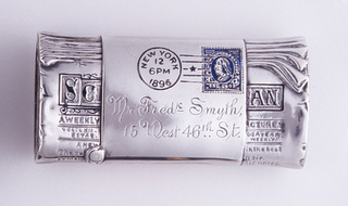 "In the form of a rolled and wrapped copy of Scientific American, front of the wrapper enameled with a New York, 1896 postmark and a blue one cent stamp, the reverse enameled with 3 red dots to simulate sealing wax. Wrapper inscribed ""Mr. Fred Smyth, 15 West 46th St."" Lid (left end of rolled paper) hinged on long, bottom edge. Both left and right ends, where paper appears to be coiled in a roll, likely also intended as strikers."