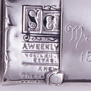 """In the form of a rolled and wrapped copy of Scientific American, front of the wrapper enameled with a New York, 1896 postmark and a blue one cent stamp, the reverse enameled with 3 red dots to simulate sealing wax. Wrapper inscribed """"Mr. Fred Smyth, 15 West 46th St."""" Lid (left end of rolled paper) hinged on long, bottom edge. Both left and right ends, where paper appears to be coiled in a roll, likely also intended as strikers."""
