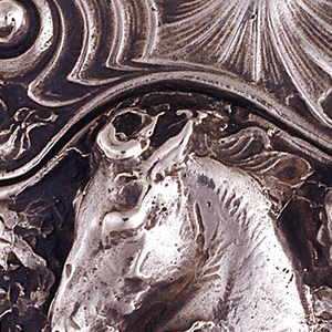 Oblong, with undulating curves on lid's uppermost edge, as well as where lid's seam meets the case body. Lid adorned with central, raised shell form, flanked by watery, nautilus-like swirls. Body features highly sculpted, relief work of a nude water nymph riding a horse amid roiling waves. Reverse of lid features same decoration as lid front. Reverse body unadorned except for a sprig of seaweed that falls downward from lid's seam, over left side of box, as well as an elaborate, intertwined monogram (possibly CK). Lid hinged on side. Slightly curved and protruding striker on bottom.